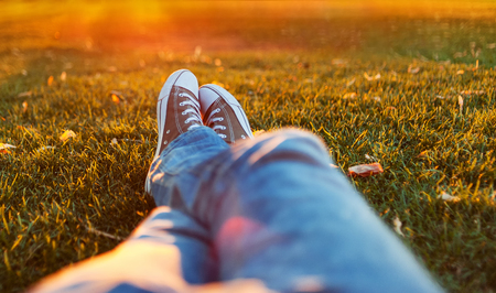 Male feet in gumshoes on green grass in the park at sunset Standard-Bild
