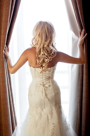 Young bride looking at window, opening curtains Stock Photo