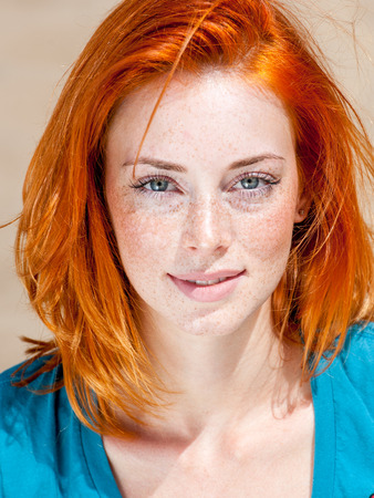 Outdoor portrait of a beautiful redhead freckled blue-eyed woman Stok Fotoğraf