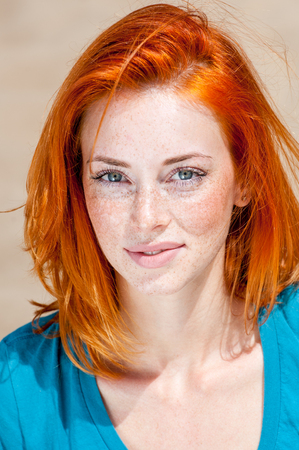 Outdoor portrait of a beautiful redhead freckled blue-eyed woman smiling Foto de archivo