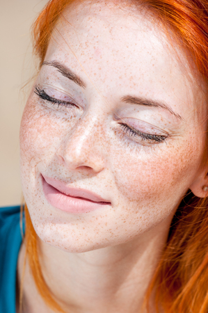 Closeup outdoor portrait of a young beautiful freckled redhead woman smiling dreamy with her eyes closed