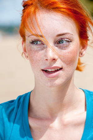 Closeup outdoor portrait of a young beautiful redhead freckled woman thinking about something