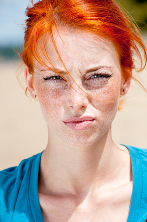 Outdoor portrait of a young beautiful redhead freckled woman looking displeased