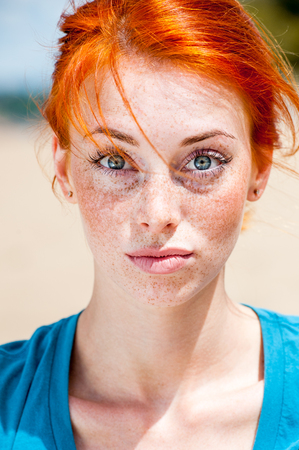 Outdoor portrait of a young funny redhead woman looking surprised