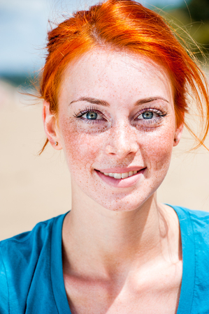 Retrato de una sonrisa pelirroja hermosa mujer joven brillante con ojos azules y pecas Foto de archivo - 100040145