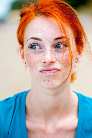 Outdoor portrait of a young redhead beautiful freckled woman thinking, pulling face