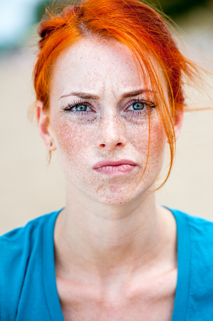 Outdoor portrait of a young redhead beautiful freckled woman looking troubled, thinking, pulling face