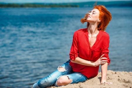 Joyful redhead woman enjoying a sunny day at the beach.