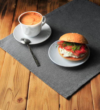 A cup of coffee and a sandwich on a wooden table Banco de Imagens