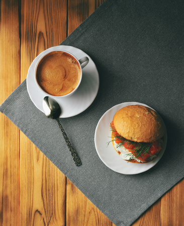 A cup of coffee and a sandwich on a wooden table, top view