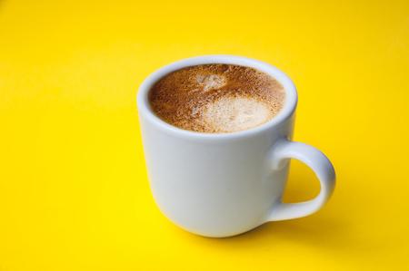 Cup of espresso, yellow backdrop
