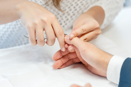 Man gets his manicure done, hands closeup