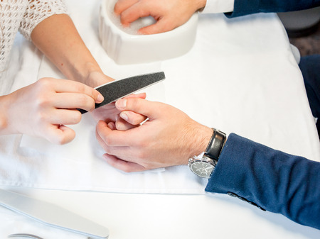 Man gets his nails done, hands closeup