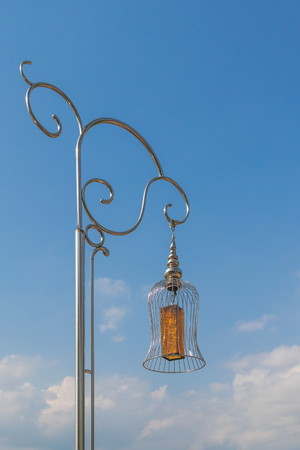 A yellow glass lamp hang up the strong street stainless lamp that the sun reflect in stainless under blue sky with clouds before sunset.