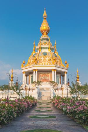 The great jewel Chedi of the Three Worlds(Thai name Wat Toong Setthi:Maha Rattana Chedi Sri Trai Lok Dhatu)with high of steeples golden Chedi under blue sky and lake side.