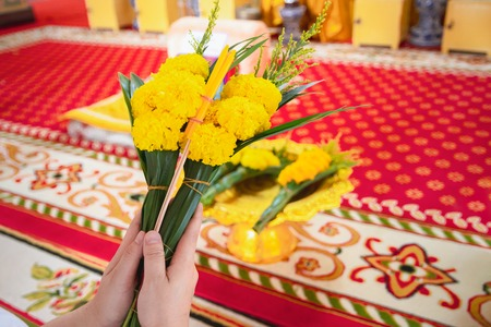 Women are using candles, flowers, incense, pray for priests in the temple.