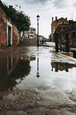 Reflection of a lamp on a puddle in Venice Italy