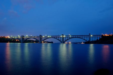 dniper: Long bridge in the night with lights reflecting in the river Dniper, Zaporizhzhya, Ukraine Stock Photo