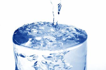 completo: Big largo gota de agua fr�a vertida en vaso lleno (aislado en fondo blanco)  Foto de archivo