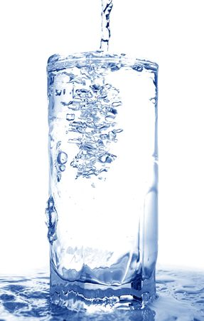 Big long drop of cold water poured into full glass (isolated on white background)