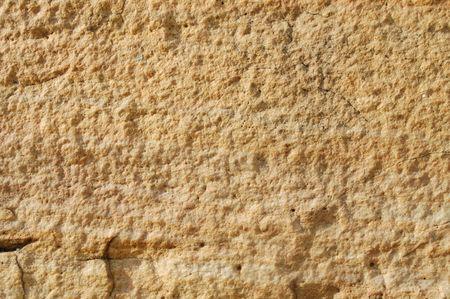 Luz de fondo de color amarillo con textura de piedra con grietas