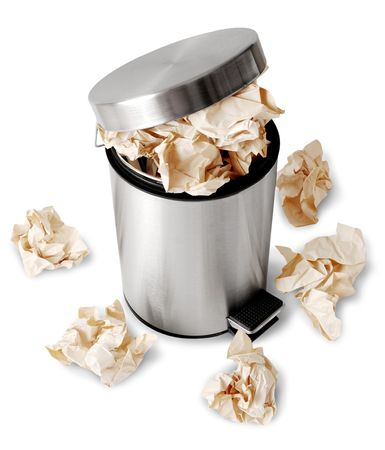 Wastebasket full up with crumpled paper. Isolated on white background photo