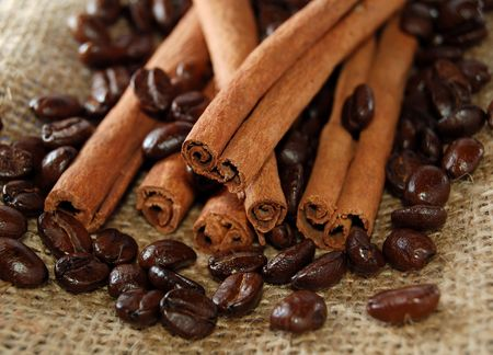 Heap of coffee beans mixed with cinnamon sticks