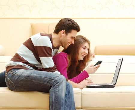 Young happy couple working on laptop photo