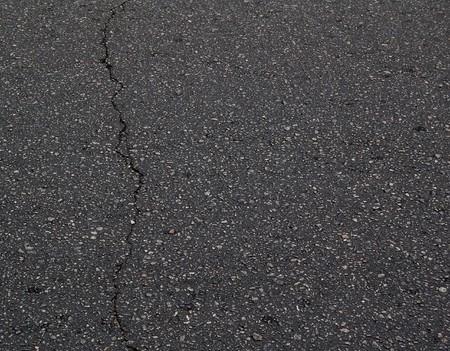 fissure: Ancien texture asphalte noir avec une fissure. Contexte asphalte avec espace pour le texte.