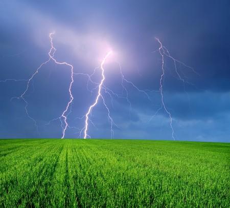 Tormenta con Lightning en campo verde  Foto de archivo