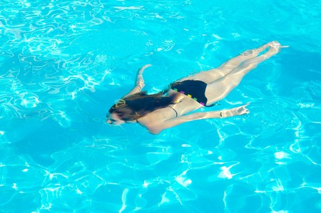 Young woman swimming underwater in the swimming pool photo
