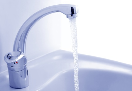 Water flowing from the faucet against the white background Stockfoto