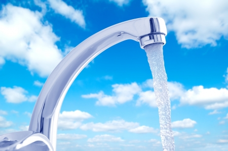 Water flowing from the faucet against the blue sky photo