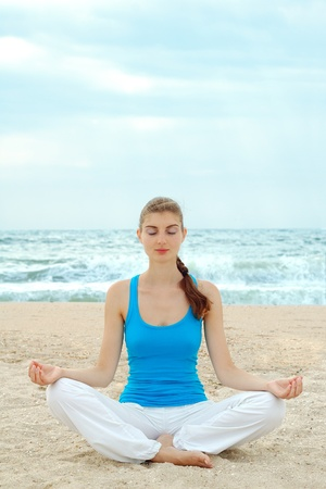 Beautiful woman practice yoga on the beach photo