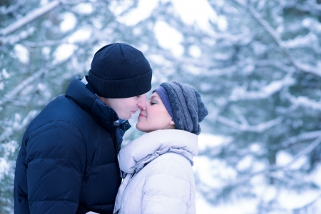 Portrait of a Young Beautiful Couple Kissing Outdoors in Snowy Winter photo