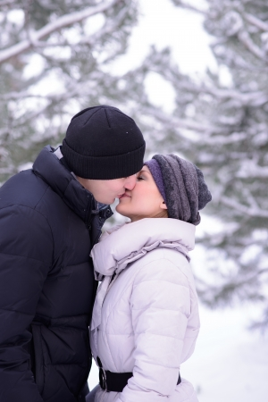 winter couple: Portrait of a Young Beautiful Couple Kissing Outdoors in Snowy Winter