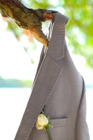 Grooms Wedding Jacket with Boutonniere Flower Hanging on a Tree Branch photo
