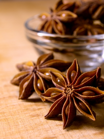 aniseed: Star Anise in the Glass Bowl on the Wooden Table Stock Photo