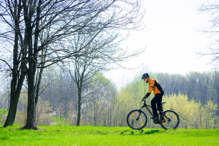 Cyclist Riding the Bike on the Green Meadow in the Forest
