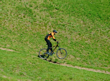 bicycle helmet: Cyclist Riding Bike Down Hill on the Rear Wheel Stock Photo