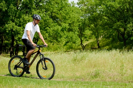 Cyclist Riding the Bike on the Trail in the Beautiful Summer Forest photo