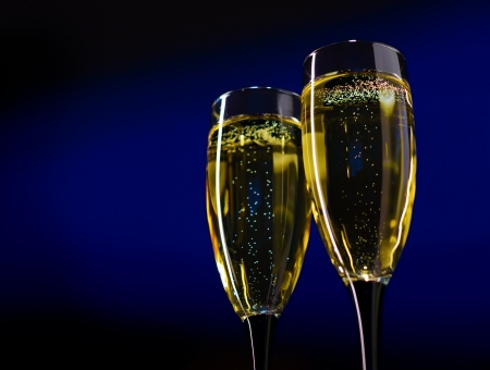 Two Glasses of Champagne Against Dark Blue Background photo