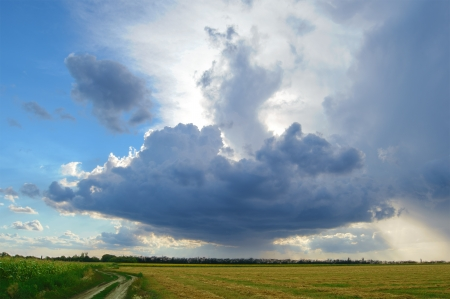 Beautiful Autumn Field under Stormy Sky with Dramatic Clouds photo