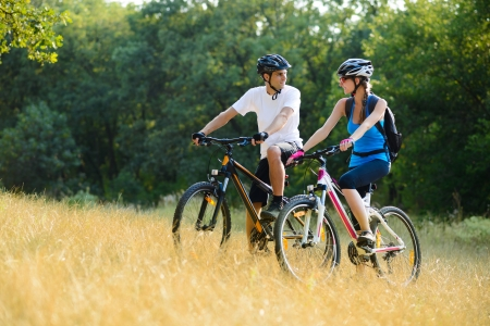 Young Happy Couple Riding Mountain Bikes Outdoor. Healthy Lifestile Concept Imagens - 21656228