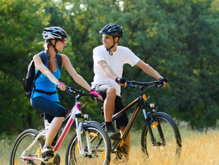 Young Happy Couple Riding Mountain Bikes Outdoor. Healthy Lifestile Concept