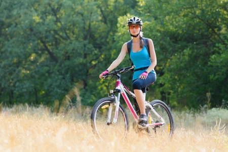 Young Attractive Woman Riding the Bike on the Beautiful Meadow in the Forest photo