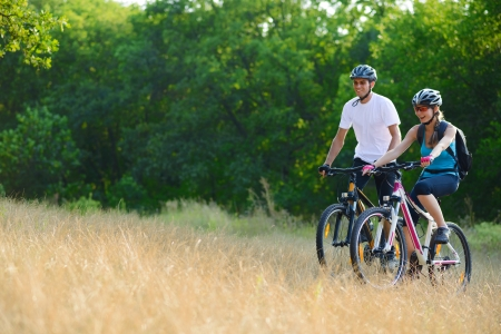Young Happy Couple Riding Mountain Bikes Outdoor  Healthy Lifestyle Concept Stock Photo