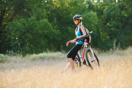 Young Attractive Woman Resting with Bike on the Beautiful Meadow in the Forest photo