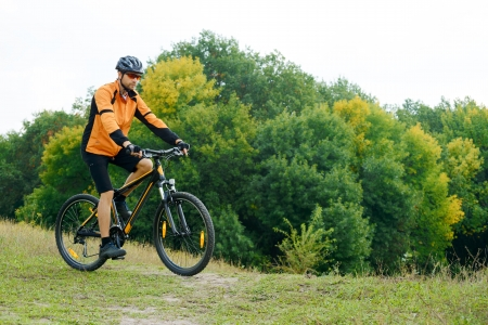 Cyclist Riding the Bike on the Trail in the Beautiful Autumn Forest photo