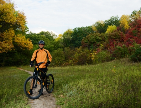 Cyclist with Bike on the Trail in the Beautiful Autumn Forest photo